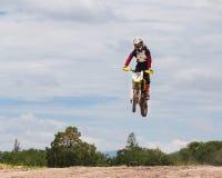做特技和跃迁在天空中的骑自行车的人的图片 免版税库存图片