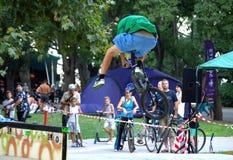 做特技的骑自行车的人在城市公园 免版税库存图片