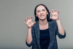 做猫的一名可怕恼怒的妇女的画象抓姿态用被举的手 库存照片