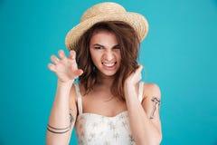 做猫的草帽的可怕恼怒的妇女抓姿态 免版税库存图片