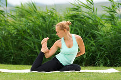 做瑜伽一只有腿的国王鸽子的妇女 库存照片
