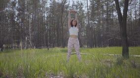 做瑜伽健身的画象健康优美的逗人喜爱的妇女舒展在森林壮观的自然 r 影视素材