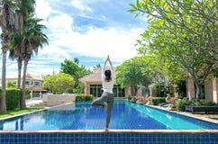 做瑜伽健身锻炼为的亚洲妇女放松和健康在游泳池背景旁边 免版税库存图片