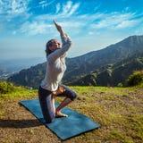 做瑜伽先进的asana的少妇 免版税库存图片