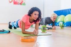 做瑜伽前臂铺板的运动的可爱的年轻女性行使或在席子的海豚姿势,当训练在健身时 免版税库存照片