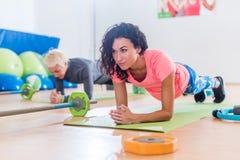 做瑜伽前臂铺板的运动的可爱的年轻女性行使或在席子的海豚姿势,当训练在健身时 免版税库存图片