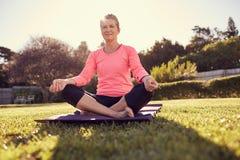 做瑜伽呼吸的锻炼的资深妇女户外与sunfla 库存图片