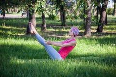 做瑜伽和体操的少妇在公园 小船姿势 库存图片