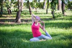 做瑜伽和体操的少妇在公园 库存照片
