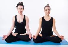 年轻做瑜伽和思考在莲花坐的人和妇女被隔绝在白色背景 库存照片