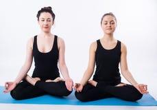 年轻做瑜伽和思考在莲花坐的人和妇女被隔绝在白色背景 图库摄影
