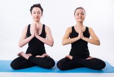 年轻做瑜伽和思考在莲花坐的人和妇女被隔绝在白色背景 免版税库存照片