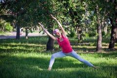 做瑜伽在公园,活跃生活方式的可爱的妇女 健康生活方式和活跃休闲的概念 免版税图库摄影