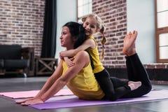 做瑜伽在地板上的年轻白种人母亲眼镜蛇姿势,当她微笑的女儿坐拥抱她的妈妈时 库存照片