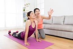 做瑜伽在客厅和舒展身体的女孩 库存图片