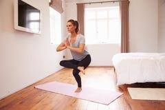 做瑜伽在席子的妇女健身锻炼在卧室 免版税库存照片