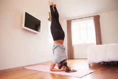 做瑜伽在席子的妇女健身锻炼在卧室 免版税库存图片