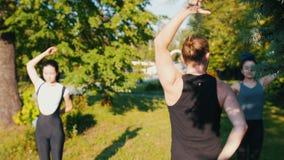 做瑜伽在有他们的辅导员的公园-举他们的手和固定它在后面的两年轻女人 影视素材