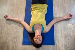 做瑜伽在锻炼席子的妇女尸体姿势 免版税库存图片