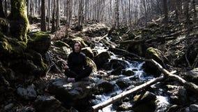 做瑜伽姿势莲花的被集中的美丽的少女坐在岩石在思考在有阳光的森林里的河 免版税库存图片