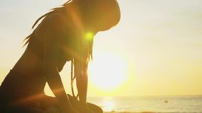 做瑜伽实践的年轻女人剪影在日落在海滩 影视素材