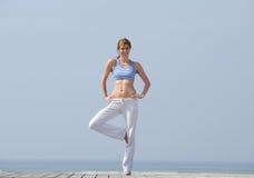 做瑜伽平衡锻炼的妇女 免版税图库摄影