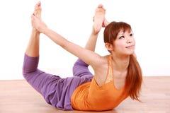 做瑜伽弓姿势的年轻日本妇女 免版税库存图片