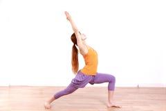 做瑜伽战士1姿势的年轻日本妇女 免版税库存图片