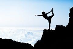 做瑜伽日落剪影的妇女 图库摄影