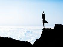 做瑜伽日落剪影的妇女 库存图片