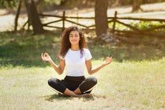 做瑜伽本质上的年轻阿拉伯妇女 免版税库存照片