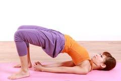 做瑜伽桥梁姿势的年轻日本妇女 免版税库存照片