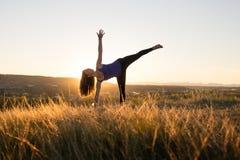 做瑜伽甲晕姿势的妇女在日落期间 库存照片