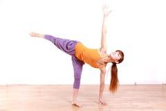 做瑜伽甲晕姿势的年轻日本妇女 库存照片