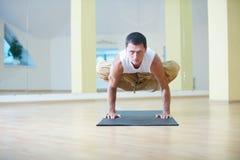 做瑜伽的一个年轻大力士在瑜伽演播室行使-帕德马Bakasana莲花起重机姿势 图库摄影
