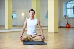 做瑜伽的一个年轻大力士在瑜伽演播室行使-莲花姿势并且思考与padmasana腿 库存照片