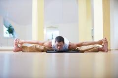 做瑜伽的一个年轻大力士在瑜伽演播室行使- Samakonasana平角姿势 库存图片