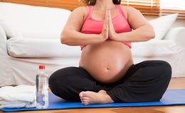 做瑜伽的一名沉重孕妇 免版税库存图片
