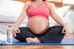 做瑜伽的一名沉重孕妇 库存照片