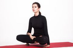 做瑜伽的一套黑衣服的美丽的运动女孩 utthita padmasana asana莲花姿势 背景查出的白色 库存图片