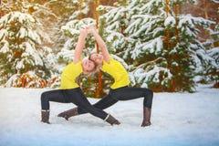 做瑜伽的两名美丽的妇女户外在雪 库存照片