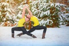 做瑜伽的两名美丽的妇女户外在雪 免版税库存照片