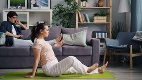 做瑜伽的主妇,当丈夫与膝上型计算机一起使用谈话在手机 股票视频