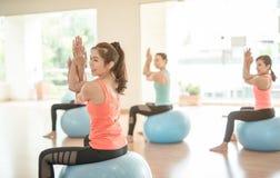 做瑜伽的亚裔妇女在瑜伽演播室 库存照片