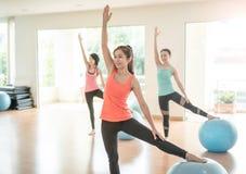 做瑜伽的亚裔妇女在瑜伽演播室 免版税库存图片