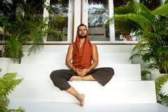 做瑜伽的人在密林在名牌服装的日落 库存照片