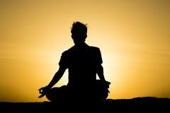 做瑜伽的人在日落点 免版税库存照片