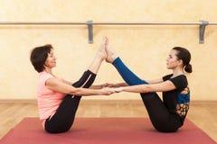 做瑜伽的女孩和成熟妇女 免版税库存图片