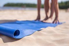 做瑜伽的女孩在一个晴天在海滩 库存照片