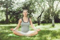 做瑜伽的女孩在公园 免版税图库摄影